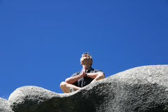 Man sits on a rock  and prays with backgrounds of bright blue sky Royalty Free Stock Images
