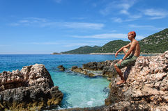Man sits on the rocky shore of Mediterranean Sea. Stock Photography