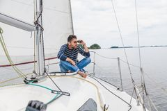 Man sits on sailing yacht and looks through binoculars Royalty Free Stock Images