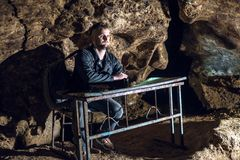 A man sits at a school desk in a dark cave. crap and perplexity on the face. Funny bad conditions for students. village Kryvche. stock photo