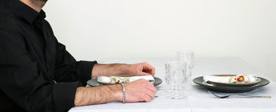 Man sits by the served table and waits Stock Photo