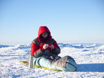 A man sits in a sleeping bag. Stock Images