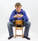 Man sits on a small wooden chair Stock Images