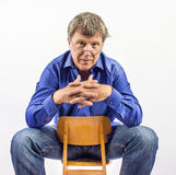 Man sits on a small wooden chair Stock Photo