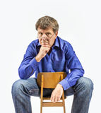 Man sits on a small wooden chair Royalty Free Stock Image