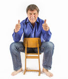 Man sits on a small wooden chair Royalty Free Stock Photography