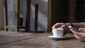 Man sits with smartphone at table with cup of coffee stock video footage