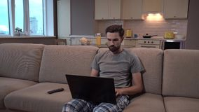 Man sits on sofa and holds laptop. He works at home. Guy is concentrated. He doesn`t distract. Man looks on screen and stock footage
