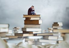 Man sits on a stack of books Stock Image