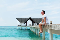 Man sits and stares into the distance on the bridge Royalty Free Stock Photos