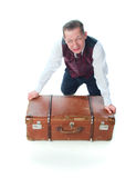 A man sits on a suitcase Stock Photos