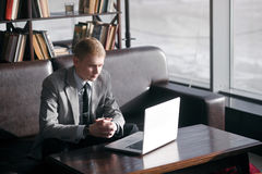 A man sits at a table with a laptop Stock Photography