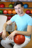 Man sits at table near shelves with balls Royalty Free Stock Photos