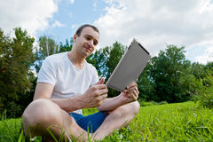 Man sits with tablet on the grass Royalty Free Stock Photo