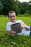 Man sits with tablet on the grass Stock Photo