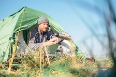 Man sits in tent and drinks hot tea stock photo