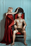 Man sits on the throne and looks at queen. Man sits on the throne and looks at the queen. Crown on their heads stock photography