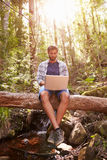 Man Sits On Tree Trunk In Forest Using Laptop Computer Royalty Free Stock Photos