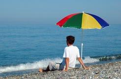 Man sits under umbrella Royalty Free Stock Image