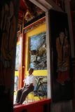 A man sits under the wall decoration of a tiger statue at the Fuk Ling Mau Temple