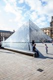 A man sits on the water feature next to the entrance to the Louvre. royalty free stock photos