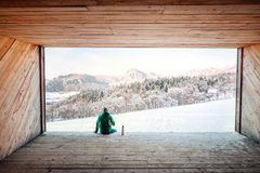 Man sits in wooden hangar wit view on snowy  mountain valley Royalty Free Stock Image