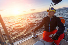 Man sits on yacht during sunset. Luxury sailing boats. Stock Images