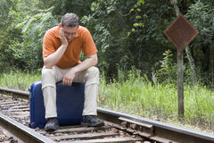 Man sittin on suitcase on railroad track Royalty Free Stock Photo