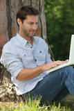 Man sitting against a tree Stock Image