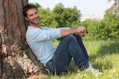Man sitting against tree Stock Photography