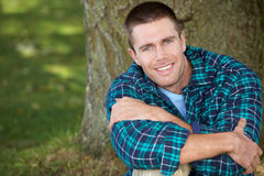 Man sitting against tree trunk Stock Photography