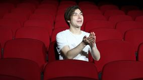 Man sitting alone and applauding in empty cinema hall or theater.  stock video