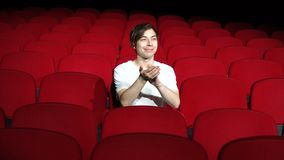 Man sitting alone and applauding in empty cinema hall or theater.  stock video footage