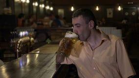 Man sitting alone at the bar in a crowded pub and large drinks beer -. Man sitting alone at the bar in a crowded pub and large drinks beer stock footage