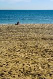 A man sitting alone on the beach royalty free stock images
