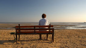 Man sitting alone on the beach stock video footage