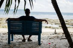 Man Sitting alone on a bench near Seashore. Waiting for someone royalty free stock photos