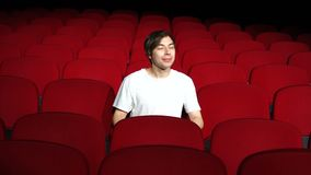 Man sitting alone in empty cinema hall or theater and watching performance or movie stock footage