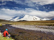 Man sitting alone on the river bank against snowy mountain and b stock photography