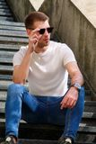 Man sitting alone on steps. Handsome boy with sunglasses. Male model posing for shooting, sitting on old stairs. Portrait of cool guy sitting on marble stock photography