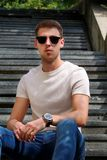 Man sitting alone on steps. Handsome boy with sunglasses. Male model posing for shooting, sitting on old stairs. Portrait of cool guy sitting on marble royalty free stock image