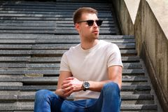 Man sitting alone on steps. Handsome boy with sunglasses. Male model posing for shooting, sitting on old stairs. Portrait of cool guy sitting on marble royalty free stock photography