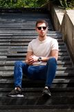 Man sitting alone on steps. Handsome boy with sunglasses. Male model posing for shooting, sitting on old stairs. Portrait of cool guy sitting on marble stock images