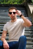 Man sitting alone on steps. Handsome boy with sunglasses. Male model posing for shooting, sitting on old stairs. Portrait of cool guy sitting on marble stock photos