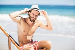 Man sitting on armchair at beach Stock Photos