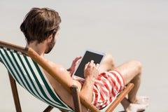 Man sitting on armchair at beach Stock Photo