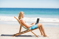 Man sitting on armchair at beach Stock Images