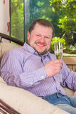 Man sitting in armchair with glass of champaign Stock Images