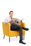 Man sitting in an armchair and holding a newspaper Stock Photography