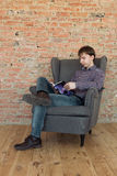 The man sitting in armchair reading book Stock Image